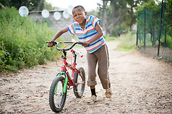 "2 March 2017, Morija, Maseru district, Lesotho: A boy walks by Scott Hospital with his bike. The hospital is run by the Lesotho Evangelical Church in Southern Africa and is a founding member of the Christian Health Association of Lesotho. It is located in the village of Morija, and operates and supervises clinics in the Maseru District of Lesotho. Scott started out as a dispensary in 1864, and today offers comprehensive healthcare Mondays-Fridays, as well as pharmaceutical services around the clock. Lesotho suffers from high numbers in Tuberculosis in disesase and mortality, and so the hospital screens all patients for TB. The hospital observes among many patients what they describe as ""low health-seeking behaviour"", services are increasing and demand rising, but space and human resources are a challenge, as is funding. I key concern is one of infrastructure, where the original design of the hospital matches poorly with current needs, as departments and buildings are scattered, posing a challenge for security. Another challenge is to adapt donation structures, so as to be able to receive payments electronically. The hospital has one ambulance, which they describe as not enough, but what they have. Another challenge is that lack of funds affects maintenance of buildings and infrastructure, as the immediate care of patients take priority. PLEASE NOTE: This photo is not to be used in social media."