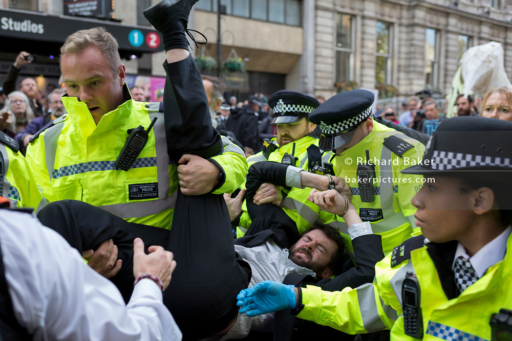 A environmental activist is arrested while protesting about Climate Change during the blockade of Whitehall in central London, part of a two-week prolonged worldwide protest by members of Extinction Rebellion, on 16th October 2019, in Westminster, London, England.