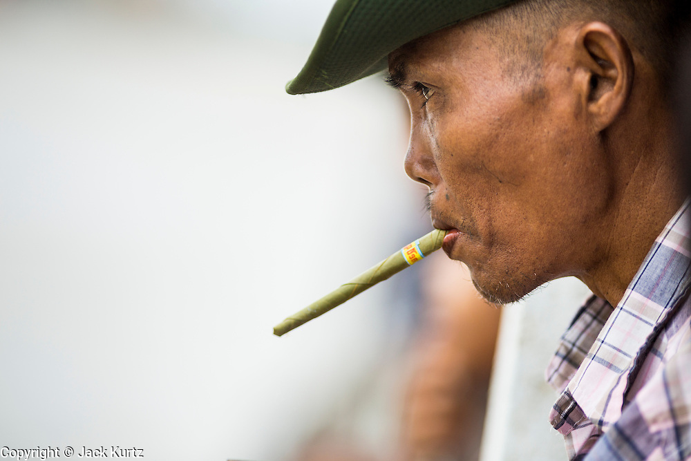 08 JUNE 2014 - YANGON, MYANMAR: A man smokes a Burmese cheroot and leans out over the Yangon River on the ferry to Dala. The ferry to Dala runs continuously through the day between Yangon and Dala. Yangon, Myanmar (Rangoon, Burma). Yangon, with a population of over five million, continues to be the country's largest city and the most important commercial center.      PHOTO BY JACK KURTZ
