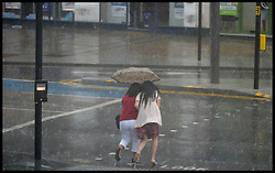 Image ©Licensed to i-Images Picture Agency. 25/07/2014. London, United Kingdom. People shelter themselfs under an umbrella in Stratford, East London, during a thunder storm . Picture by Andrew Parsons / i-Images