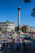Tourists and Londoners enjoy a summers day around the fountains of Trafalgar Square, London.