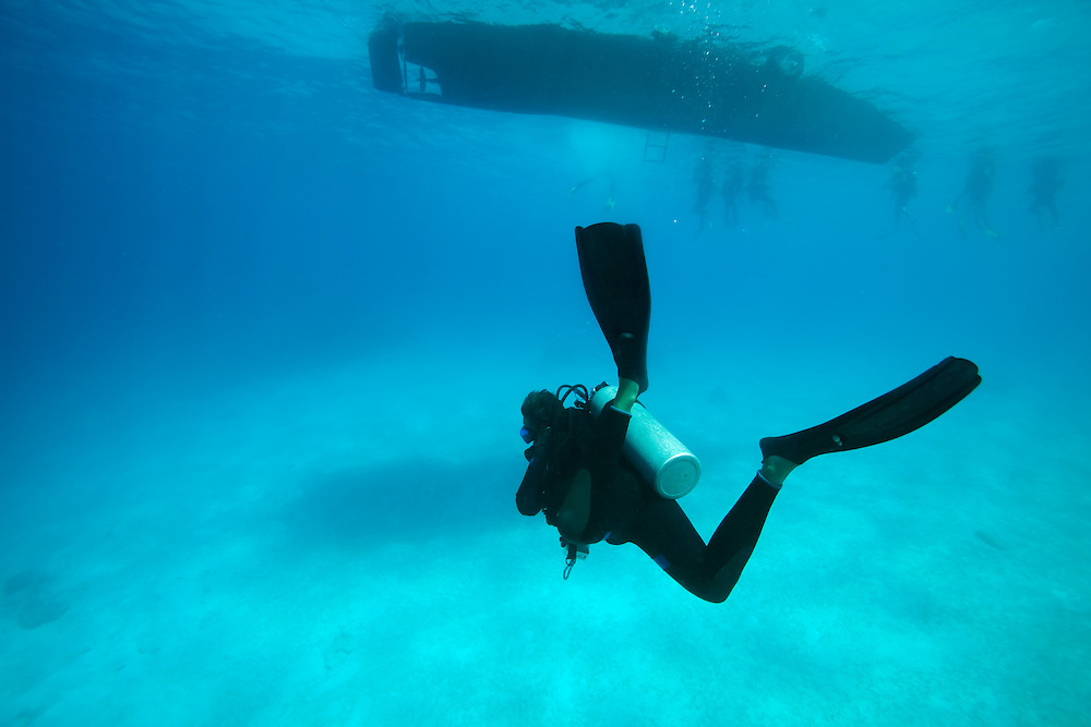 Africa, Tanzania, Zanzibar, Matemwe Bay, Young woman scuba diving from charter boat into Indian Ocean