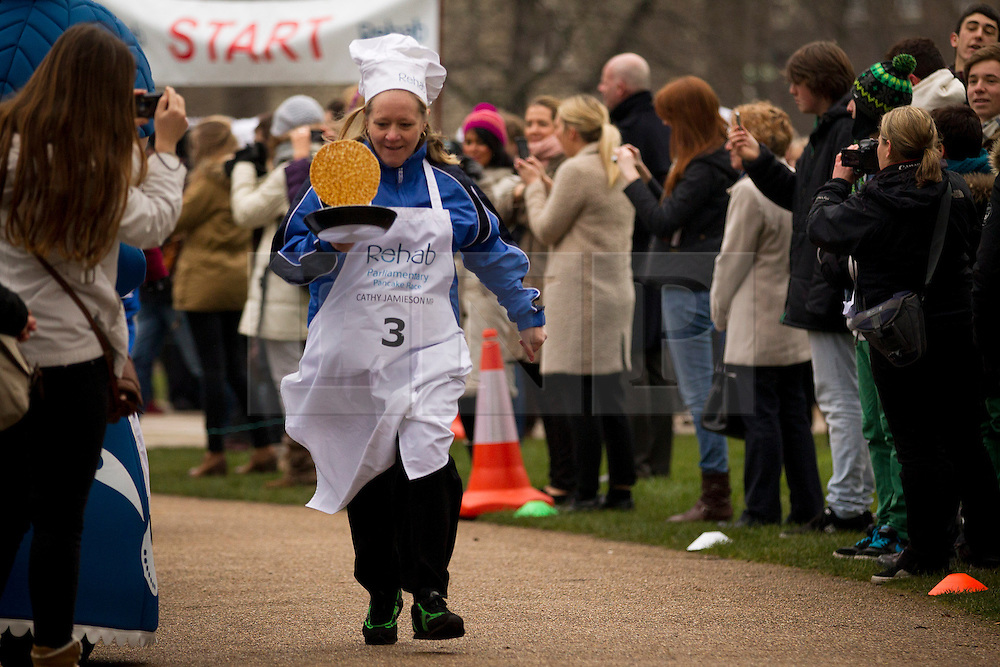 © Licensed to London News Pictures. 12/02/2013. London, UK. Scottish Labour MP Cathy Jamieson tosses a pancake as she takes part in the annual Rehab Parliamentary Pancake Race in Westminster London today (12/02/2013). The race involving MPs from the House of Commons, Lords from the House of Lords and members of the Parliamentary Press Gallery, is aimed at raising awareness for the Rehab; a charity that works to support people with disabilities, takes place every year in Victoria Tower Gardens next to Parliament and was won this year by the House of Commons team. Photo credit: Matt Cetti-Roberts/LNP