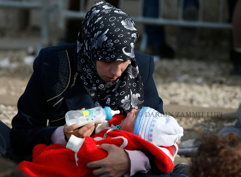 A migrant bottle feeds her baby as refugees and migrants wait to continue their journey towards western Europe from the Macedonia-Serbia border at a transit camp in the village of Presevo, Serbia, February 2, 2016.<br /> Photo: Darrin Zammit Lupi