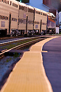 As the sun sets, a westbound Metra commuter train pulls out of the New Lenox, IL depot.