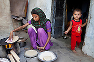 Sadma Khan (in purple), 19, makes lunch while her 18 month old son stands at her door in the shared compound of her mother's extended family's house in a slum area of Tonk, Rajasthan, India, on 19th June 2012. She was married at 17 years old to Waseem Khan, also underaged at the time of their wedding. The couple have an 18 month old baby and Sadma is now 3 months pregnant with her 2nd child and plans to use contraceptives after this pregnancy. She lives with her mother since Waseem works in another district and she can't take care of her children on her own. Photo by Suzanne Lee for Save The Children UK