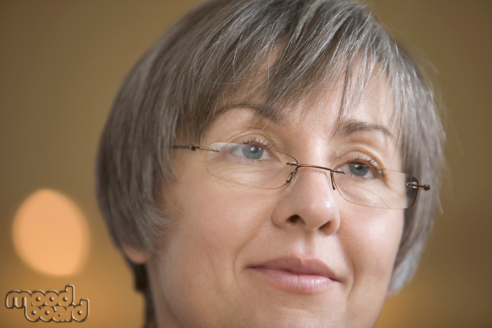 Mature woman with short grey hair  in spectacles