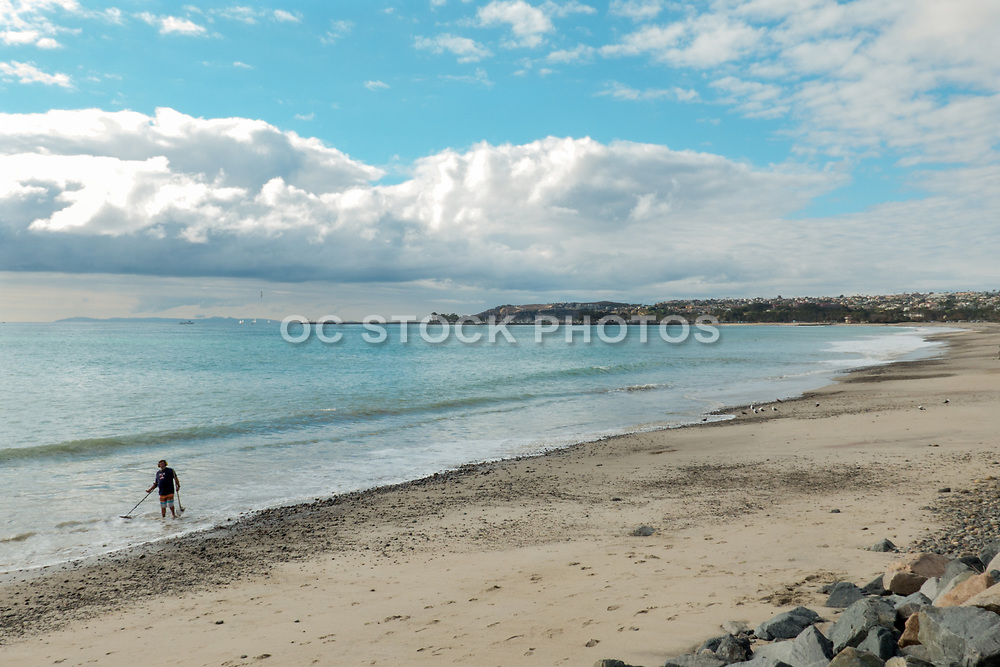 A Man Walking On The Beach Using A Metal Detector In Dana Point