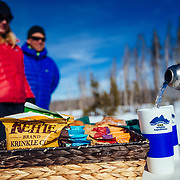 Clients eat snacks and drink coffee along Yellowstone Lake on a winter tour through the park.