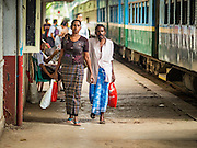 26 OCTOBER 2015 - YANGON, MYANMAR:  People walk through Yangon Central Railroad Station after arriving in Yangon on the Circular Train. The Yangon Circular Railway is the local commuter rail network that serves the Yangon metropolitan area. Operated by Myanmar Railways, the 45.9-kilometre (28.5 mi) 39-station loop system connects satellite towns and suburban areas to the city. The railway has about 200 coaches, runs 20 times daily and sells 100,000 to 150,000 tickets daily. The loop, which takes about three hours to complete, is a popular for tourists to see a cross section of life in Yangon. The trains run from 3:45 am to 10:15 pm daily. The cost of a ticket for a distance of 15 miles is ten kyats (~nine US cents), and for over 15 miles is twenty kyats (~18 US cents).    PHOTO BY JACK KURTZ