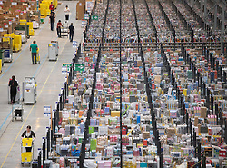 © London News Pictures. 28/11/2013. Peterborough, UK. An aerial view of items on shelves waiting to be distributed. Staff at the Amazon Peterborough fulfilment centre process orders as they prepare for 'Cyber Monday', busiest online shopping day of the year. On Cyber Monday 2012, Amazon.co.uk saw more than 3.5 million items ordered on the site, at a rate of around 41 items per second. Over 15000 extra staff are drafted in to Amazon nation wide over the festive period to cope with the extra demand with over 1000 extra staff being deployed at the Peterborough site. Photo credit: Ben Cawthra