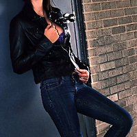 Young woman posing in leather jacket and jeans.
