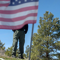 Navajo Nation Police Officer James Hale poses  fora photo at the memorial shrine for Officer Alex Yazzie Wednesday around mile 14.5 on Indian Service Route 13 near Red Valley. Officer Hale was wounded during the same incident that Officer Yazzie lost his life March 19, 2015.