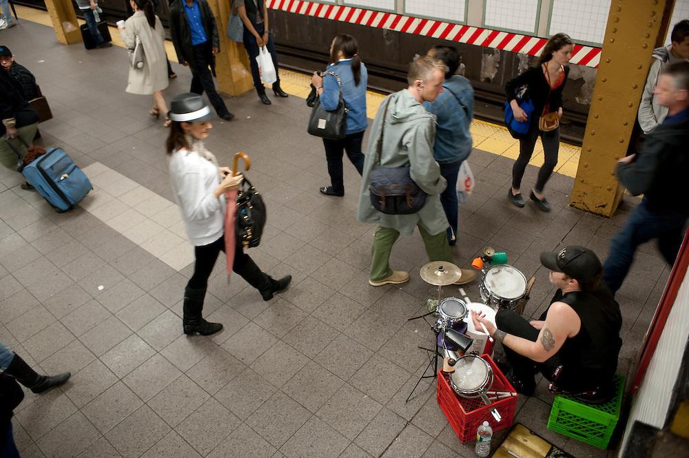 Schlagzeuger Mike Alaska in der Union Square Station in Manhattan. Die L Ubahn Linie mit seinen oft jungen Fahrgaesten zieht viele Musiker an...Jedes Jahr im Mai laden die Betreiber der New Yorker Subway (MTA) ca 60 Musiker und Gruppen zu einem Wettbewerb im Grand Central Station ein. Die Gewinner duerfen ganz legal an ihnen zugeteilten Orten im Ubahn System auftreten. Viele unangemeldete  und selbst organisierte Musiker jeder nur erdenklichen Musikrichtung spielen zudem in fast jeder wichtigen Ubahnstation. Die Angst vor der Polizei ist dabei gering, selten gibt es eine Verwarnung und noch seltener ein Bussgeld. Meist wird einfach der Ort gewechselt falls es Probleme gibt...Drummer Mike Alaska on the L train platform at Union Square Station in Manhattan. The L train attracts many musicians...MTA (Metropolitan Transportation Authority) .Music Under New York.Auditions.Every Spring, Music Under New York (MUNY) presents a day of auditions in Grand Central Terminal to review and add new performers to the MUNY roster. This year, MUNY held its annual auditions in May on the Northeast Balcony of the Grand Central Terminal. .In addition legions of non-official musicians play in New Yorks subway stations and on platforms. One can find every thinkable style and instrument underground. ..Foto: Stefan Falke.