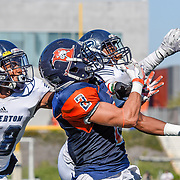 Costa Mesa, California --Orange Coast College Receiver Joey Cox attempts to catch an incoming pass from Fullerton College's defensive end Daniel Robinson during Saturday's game at LeBard Stadium.