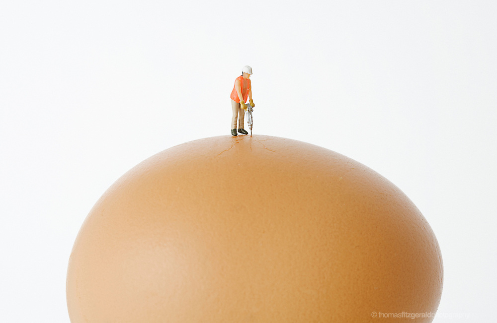 An Abstract Metaphor of a Tiny Construction worker cracking open an egg shell
