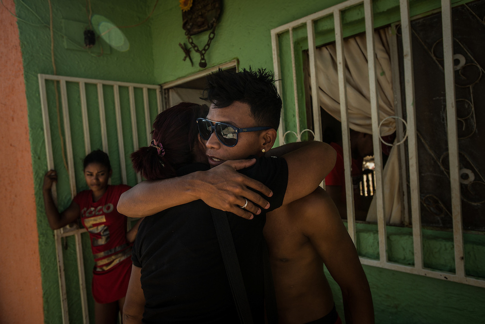 LA VELA, VENEZUELA - SEPTEMBER 18, 2016: Maria Pi&ntilde;ero says goodbye and hugs her son, Roger Bello (right) and his girlfriend Yaisbel, (left) who is 6 months pregnant. Roger plans to make the trip to Curacao soon as well, in order to support Yaisbel and their baby. The wait is agonizing.  Smugglers tell migrants to be ready to leave any minute, but made them wait for weeks, delaying the departure date over 8 times. To escape the economic crisis in Venezuela, Ms. Pi&ntilde;ero spent all of her savings to pay smugglers to take her in a small fishing boat to Curacao island. &ldquo;I&rsquo;m nervous,&rdquo; she said. &ldquo;I&rsquo;m leaving with nothing. But I have to do this. Otherwise, we will just die here hungry.&rdquo;<br /> Despite having the largest known oil reserves in the world, Venezuela is suffering from hyperinflation and a severe economic crisis making affordable food difficult for most middle and working class families to access.  Well over 150,000 Venezuelans have fled the country in the last year alone, the highest in more than a decade, according to scholars studying the exodus. As Hugo Ch&aacute;vez&rsquo;s Socialist-inspired revolution collapses into economic ruin, as food and medicine slip further out of reach, the new migrants include the same impoverished people that Venezuela&rsquo;s policies were supposed to help. &ldquo;We have seen a great acceleration,&rdquo; said Tom&aacute;s Paez, a professor who studies immigration at the Central University of Venezuela. He says that as many as 200,000 Venezuelans have left in the last year, driven by how much harder it is to get food, work and medicine &mdash; not to mention the crime such scarcities have fueled.  PHOTO: Meridith Kohut for The New York Times
