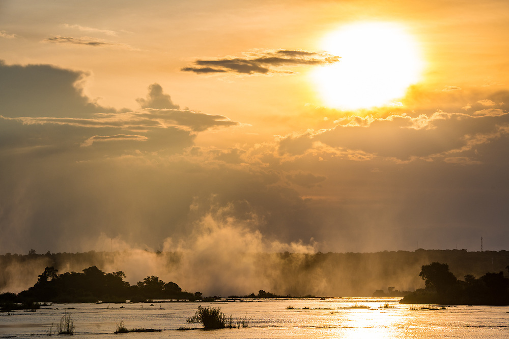 Steam rises from the Zambezi River as the sun sets over the water in Livingstone, Zambia