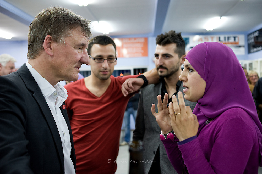 A young Muslim woman discusses the headscarf issue with Antwerp mayor Patrick Janssens after an election debate held by a union of minority organizations. Antwerpen, Belgium, 2012
