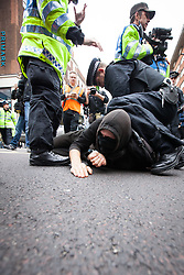 © Licensed to London News Pictures . FILE PHOTO DATED 20/10/2012 of a Black Bloc protester being detained by police on Oxford Street at a demonstration in London as reports circulate that black bloc tactics may be employed by protesters seeking to demonstrate during the funeral of former British Prime Minister Margaret Thatcher . Photo credit : Joel Goodman/LNP