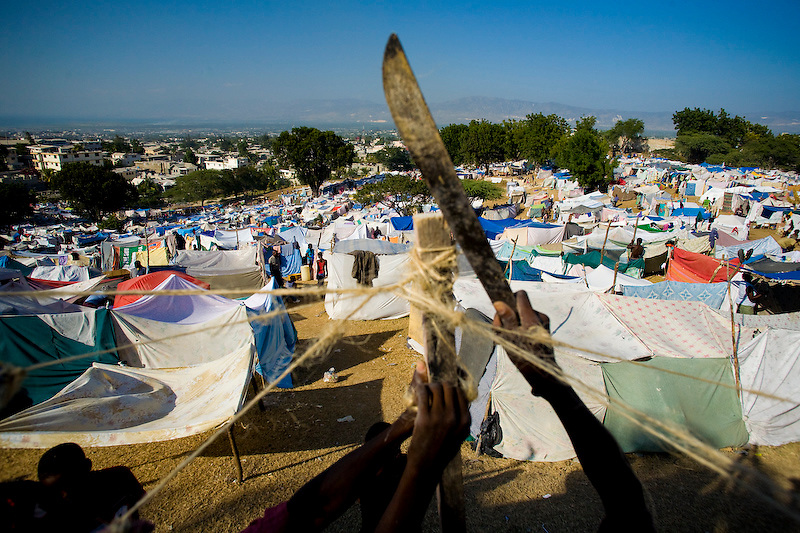 Displaced Haitians build themselves temporary shelter on a golf course. Port Au Prince, Haiti. Photo by Ben Depp.1/22/2010.