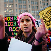 A protester gives the middle finger while marching past Trump International Hotel, Washington, D.C., during the Women's March on Washington