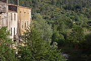 Travellers rest in sunlight on a balcony overlooking French countryside, on 21st May 2017, in Lagrasse, Languedoc-Rousillon, south of France. Lagrasse is listed as one of France's most beautiful villages and lies on the famous Route 20 wine route in the Basses-Corbieres region dating to the 13th century.