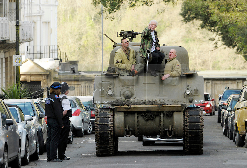 &copy; Licensed to London News Pictures. 09/04/2014; Bristol, UK.  Tony Miles, (white hair and glasses) aka Smiley Miley from the Radio 1 Roadshow, rides in a WW2 Sherman tank through local streets in a protest by residents and traders from Clifton Village in Bristol about plans for a Residents Parking Scheme in their area from Bristol's elected Mayor, George Ferguson.  They say the business and social life of the area will be hit very hard by the RPS with customers and visitors unable to park, and that some businesses will have to close or move away from the area.  The tank is a symbol of defending their area against RPS.<br /> Photo credit: Simon Chapman/LNP