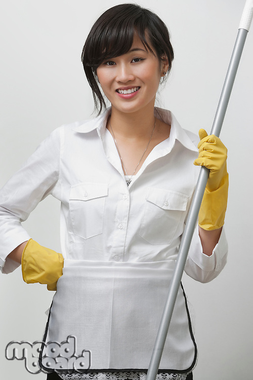 Portrait of young housemaid holding mop against gray background