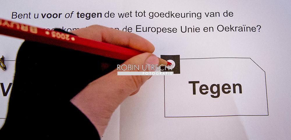 eigen rotterdam  - stemmen , DEN HAAG - Een rood stempotlood in een stemlokaal.  ja of nee brengt een stem uit tijdens het referendum over het associatieverdrag van de EU met Oekraine. op de basischool de walvis   beveiling beveiligers , bewaken , politie , politieagent , copyright robin utrecht