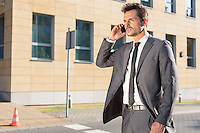 Handsome young businessman using cell phone outdoors
