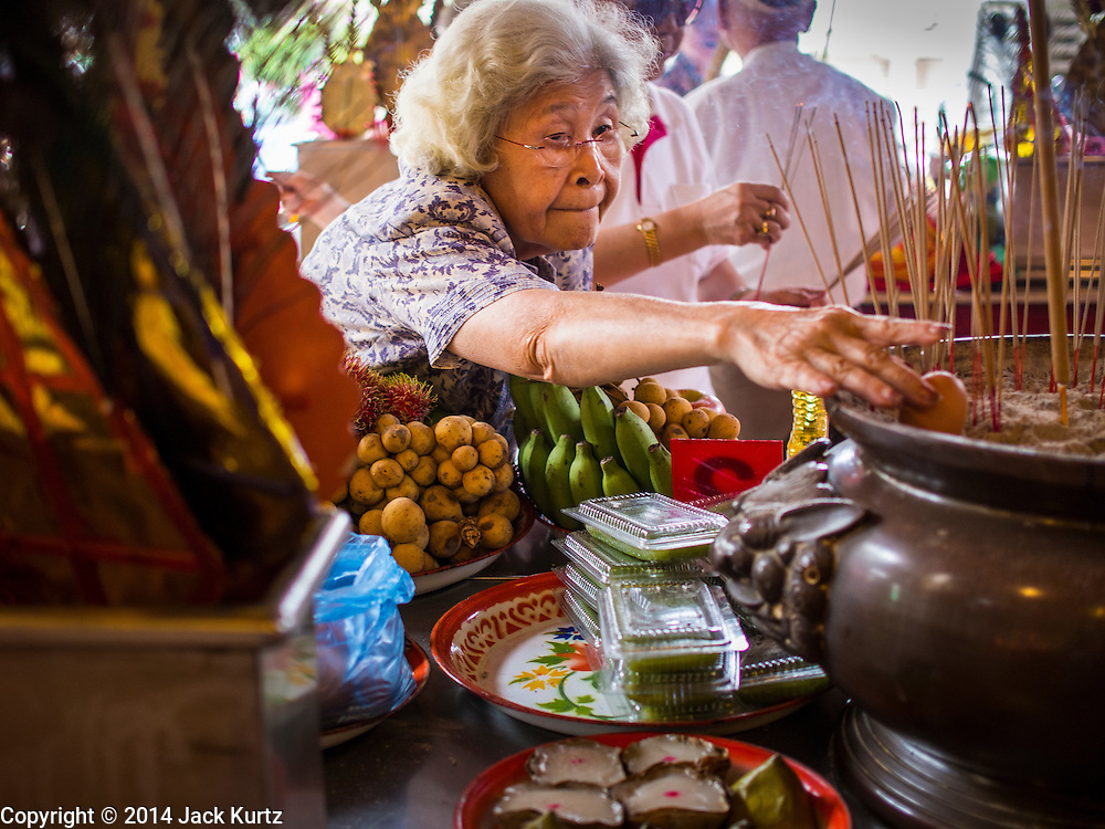 "07 AUGUST 2014 - BANGKOK, THAILAND: A woman leaves ceremonial food at an alter Pek Leng Keng Mangkorn Khiew Shrine. Thousands of people lined up for food distribution at the Pek Leng Keng Mangkorn Khiew Shrine in the Khlong Toei section of Bangkok Thursday. Khlong Toei is one of the poorest sections of Bangkok. The seventh month of the Chinese Lunar calendar is called ""Ghost Month"" during which ghosts and spirits, including those of the deceased ancestors, come out from the lower realm. It is common for Chinese people to make merit during the month by burning ""hell money"" and presenting food to the ghosts. At Chinese temples in Thailand, it is also customary to give food to the poorer people in the community.     PHOTO BY JACK KURTZ"