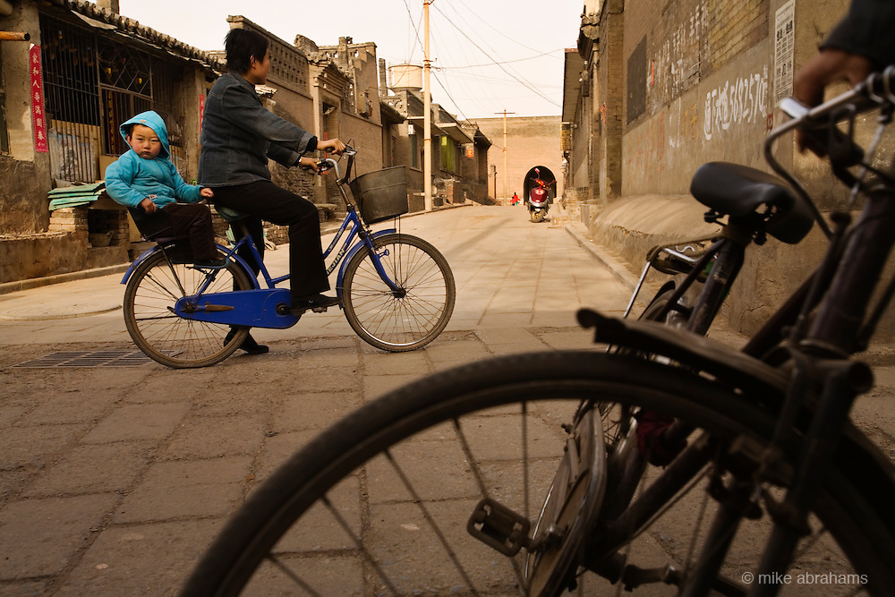 A baby on the back of a bicycle, Pinghao, People's Republic of China