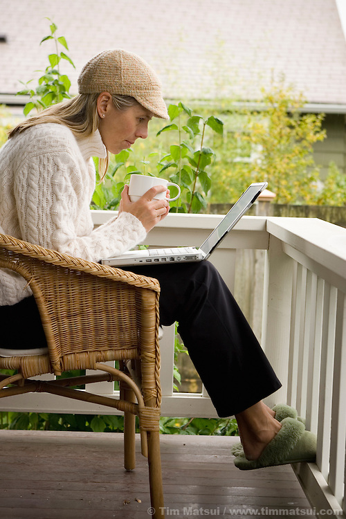 A caucasian woman sits alone on a porch in the morning drinking coffee with her wireless, wi-fi, laptop computer.