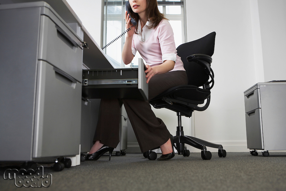 Woman sitting behind desk in office using phone and opening drawer