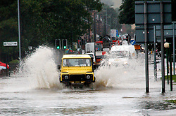 A Yellow Landrover drives through the flooding on The Common Ecclesfield Sheffield South Yorkshire.25 June 2007.Image COPYRIGHT Paul David Drabble.