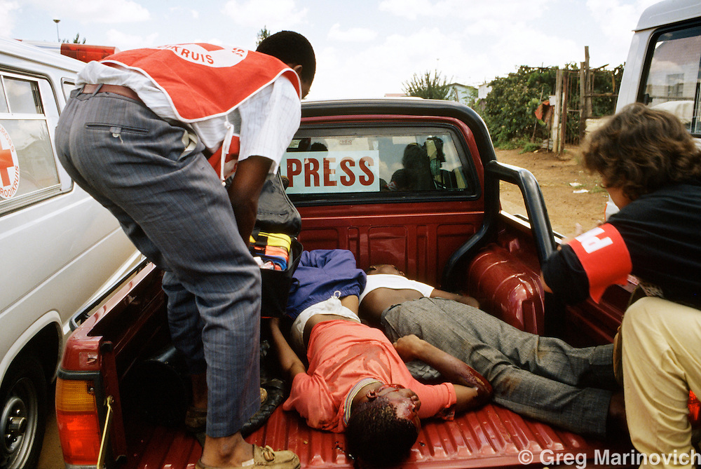 Bekkersdal, Transvaal, South Africa 1994. Peace monitors load the bodies of people killed in clashes between police, army, Azapo and the ANC is Bekkersdal township, 1994, onto an SABC pickup truck.