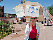 Aug. 8, 2009 -- SCOTTSDALE, AZ: GINA CIZEK, from Phoenix, AZ, uses an umbrella for shade and to express her opposition to the Obama health care reform plan in Scottsdale, AZ, Saturday. Nearly 1,000 people opposed to the President Barack Obama's health care reform efforts picketed the offices of Congresman Harry Mitchell (D-AZ) in Scottsdale, AZ, Saturday. The protest was organized by conservative groups who are organizing similar protests against President Obama across the US. Ostensibly concerned mostly with health care reform, it was also a protest against almost everything related to the Obama administration. Photo by Jack Kurtz / ZUMA Press