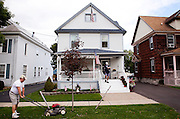 AUBURN, NY – SEPTEMBER 15, 2010: A man mows his front lawn while the postman delivers mail.