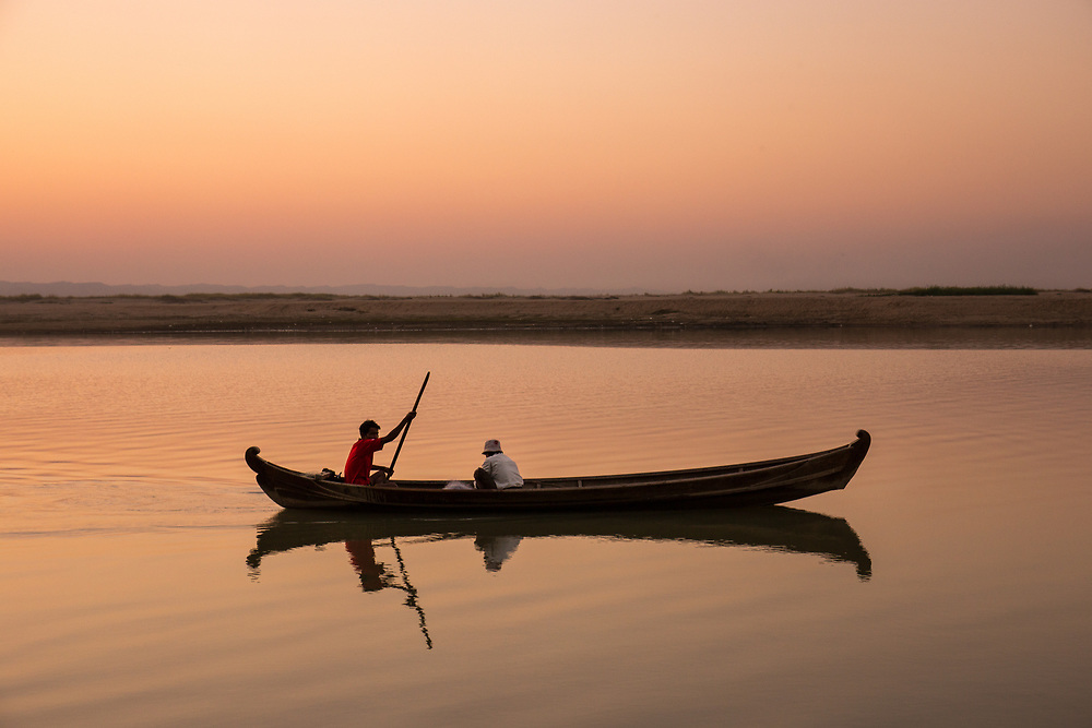 Two friends on a wooden canoe are sailing at dusk on the calm water of the Irrawaddy River in Myanmar.                     Photo by Lorenz Berna
