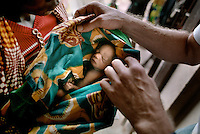 ©BURUNDI 2004. A mother brings her baby, prematurely born in the night, to a health clinic for consultation..Picture featured in book KIDS photos by Markus Marcetic, published 2007.