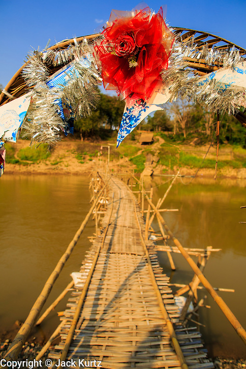 11 MARCH 2013 - LUANG PRABANG, LAOS: The bamboo foot bridge over the Nam Khan River in Luang Prabang is a seasonal bridge. It's built when the river level recedes in the dry season and washes away every year when the river rises. It connects Luang Prabang to several small villages north of the city.    PHOTO BY JACK KURTZ