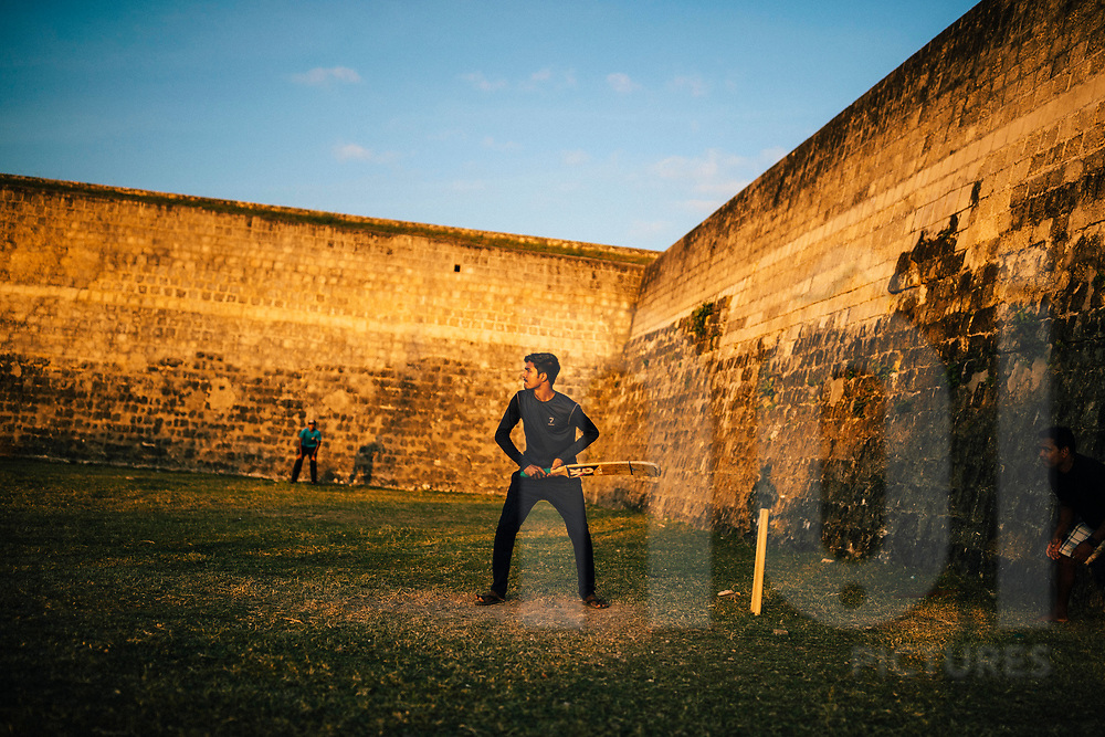 Cricket players in the late afternoon sun at Jaffna Fort, Sri Lanka, Asia