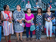 04 JULY 2019  - DES MOINES, IOWA: LUCRETIA WALWEH KOFFA, left, originally from Liberia, LALMUAN PUII, originally from Myanmar, AASHA RAI, from Bhutan, LISA WAPOH WASHINGTON, from Liberia, and MJ VENTURA LIBANAN, originally from the Philippines, wait for their naturalization ceremony to start before the Iowa Cubs game. Thirty people became US citizens during a naturalization ceremony at the Iowa Cubs game in Des Moines. The naturalization ceremony is an Iowa Cubs 4th of July tradition. This is the 11th year they've held the ceremony.          PHOTO BY JACK KURTZ