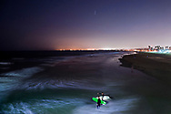 September 10, 2014 - Two surfers eye the waves before heading out for some night riding near the Huntington Beach Pier in Huntington Beach, CA.