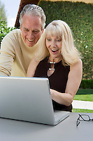 Surprised couple using laptop in back yard