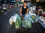 01 DECEMBER 2016 0 BANGKOK, THAILAND: A porter loads up his handtruck at the traditional market on Lan Luang Road in Bangkok. The market is on the site of one of the first western style cinemas in Bangkok. The movie theatre closed years ago and is still empty but the market fills the streets around the theatre.     PHOTO BY JACK KURTZ