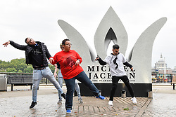 "© Licensed to London News Pictures. 29/08/2018. LONDON, UK.  Michael Jackson fans dance to ""Thriller ""next to a 13 foot high jewelled crown which has been installed on the South Bank to mark Michael Jackson's 60th birthday.  Photo credit: Stephen Chung/LNP"