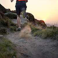 A photograph of a fell runner kicking up dust while running on heathland on Ilkley Moor, Yorkshire, England