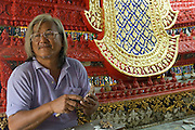 A craftsman at work on restoration of the altar. Restoration work in progress at Wat Saothongtong.